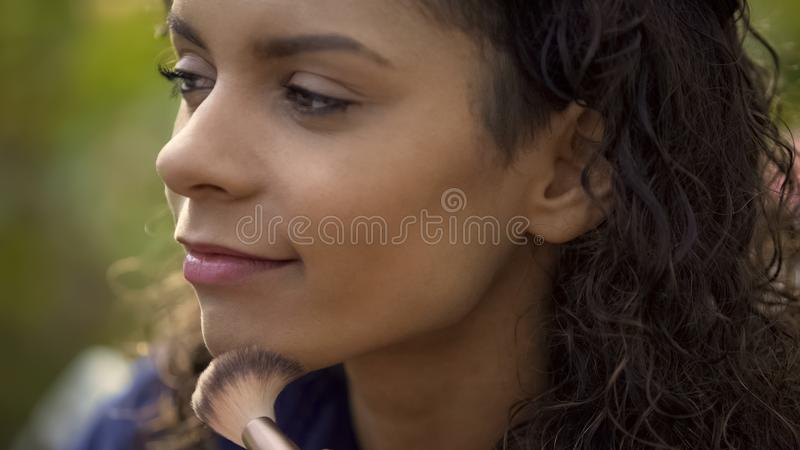 Professional makeup artist evens up model skin tone with brush, movie shooting stock photos