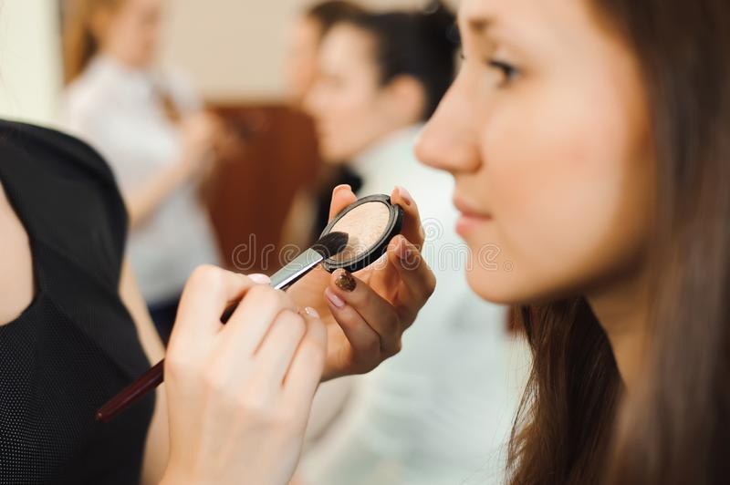 Professional makeup artist working with beautiful young woman. royalty free stock photo