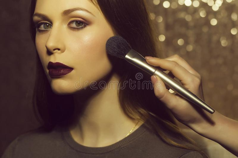 Professional makeup artist working with beautiful young woman royalty free stock photo