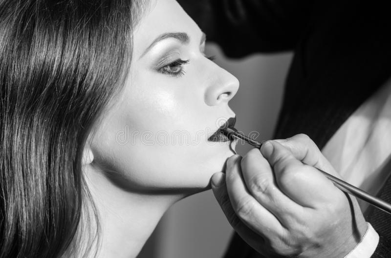 Professional makeup artist working with beautiful young woman stock photography