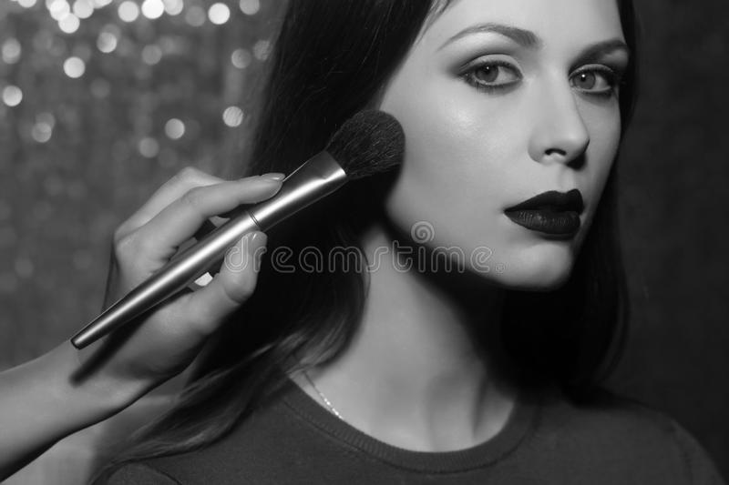 Professional makeup artist working with beautiful young woman stock image