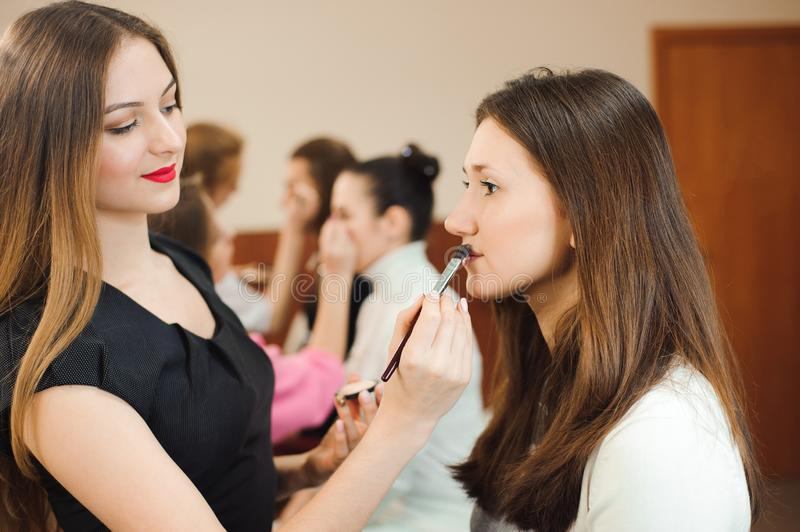 Professional makeup artist working with beautiful young woman royalty free stock photos