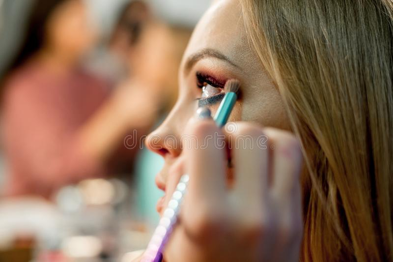 Professional makeup artist working on young girl stock image