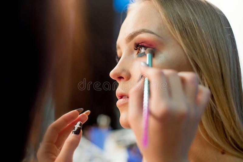 Professional makeup artist working on young girl royalty free stock images