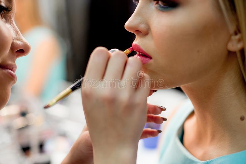 Professional makeup artist working on young girl royalty free stock photos