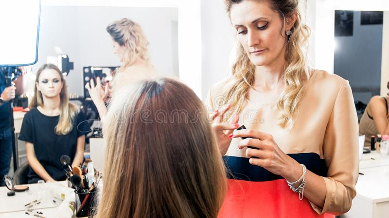 Professional makeup artist working with young model in beauty salon stock images