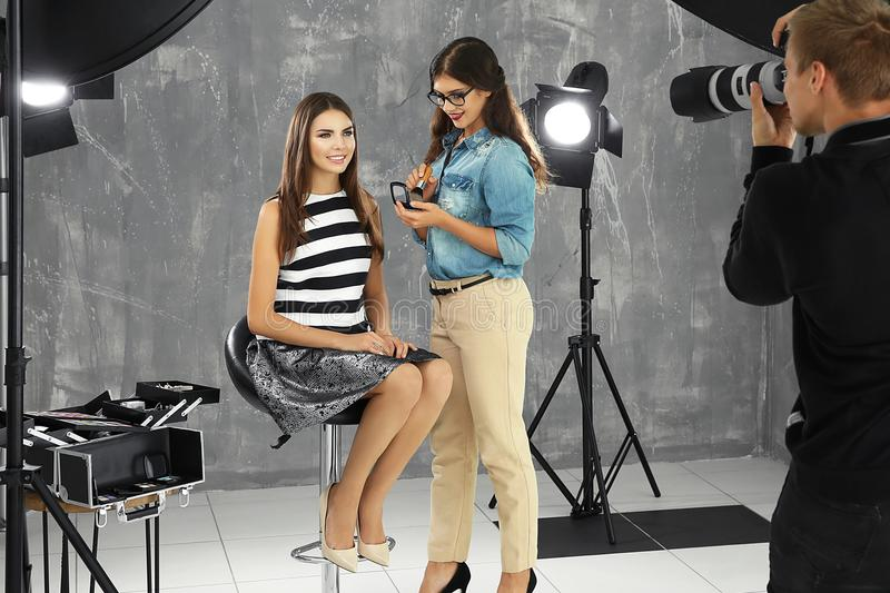 Professional makeup artist working with young woman at photo shooting royalty free stock photos