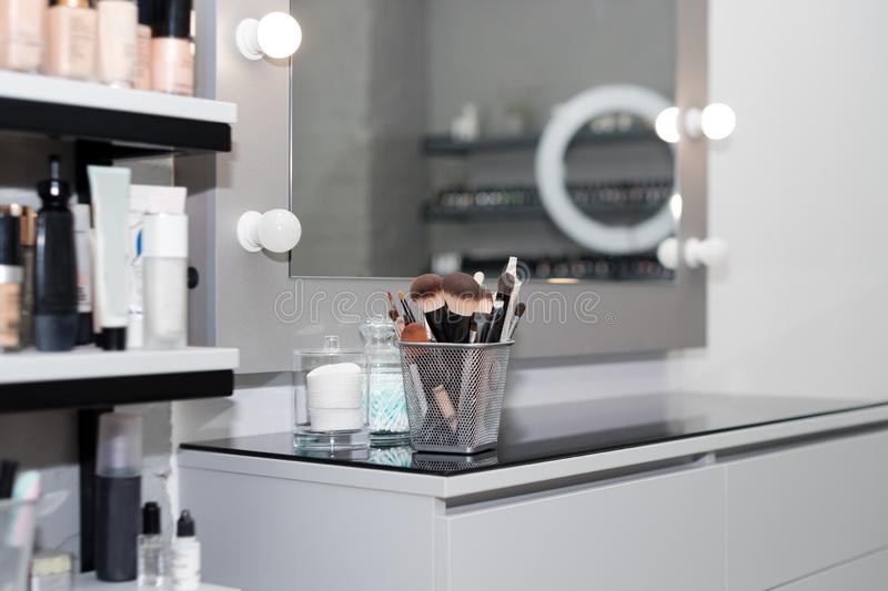 Professional makeup brushes set closeup near salon mirror. Brush any size for professional make-up artist on blur royalty free stock photography