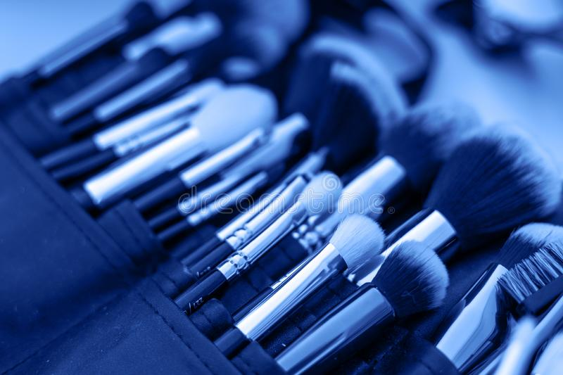 Professional makeup brushes and tools, make-up products set. Image monochrome toned. Color of the year. Beautiful blue background stock photography