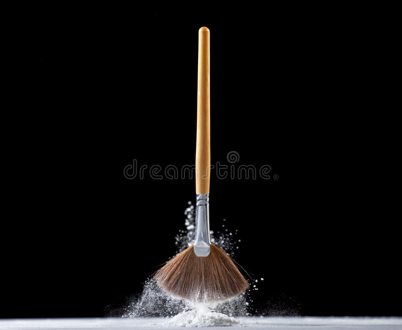 Professional makeup fan brush. Thick professional fan brush and loose white powder particles stock images