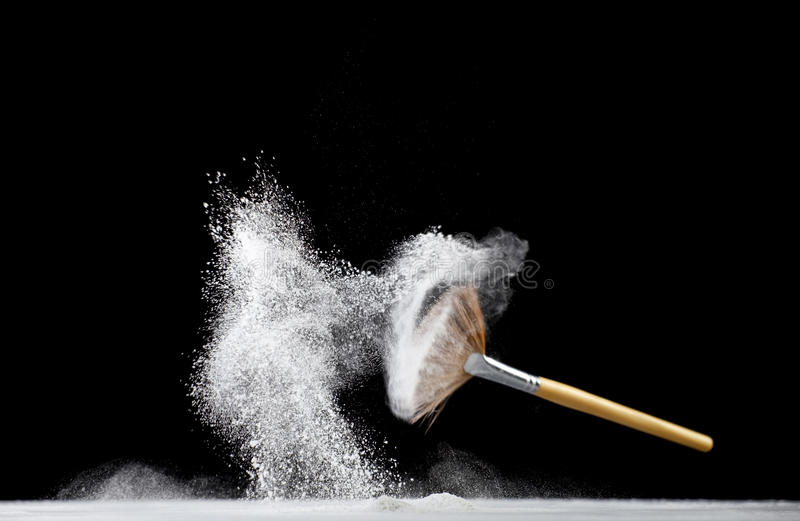 Professional makeup fan brush. Thick professional fan brush and loose white powder particles stock photography