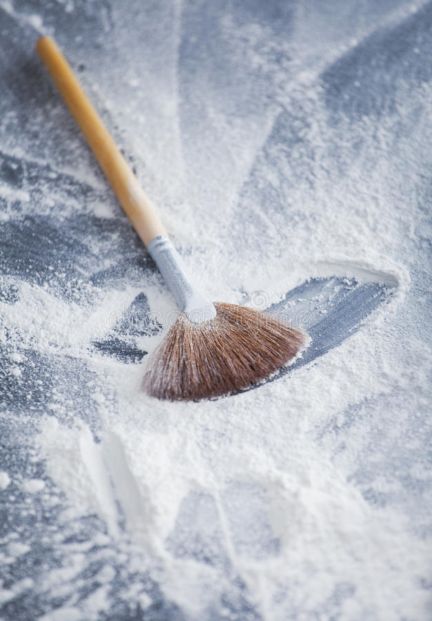 Professional makeup fan brush. Thick professional fan brush and loose white powder particles scattered around stock image