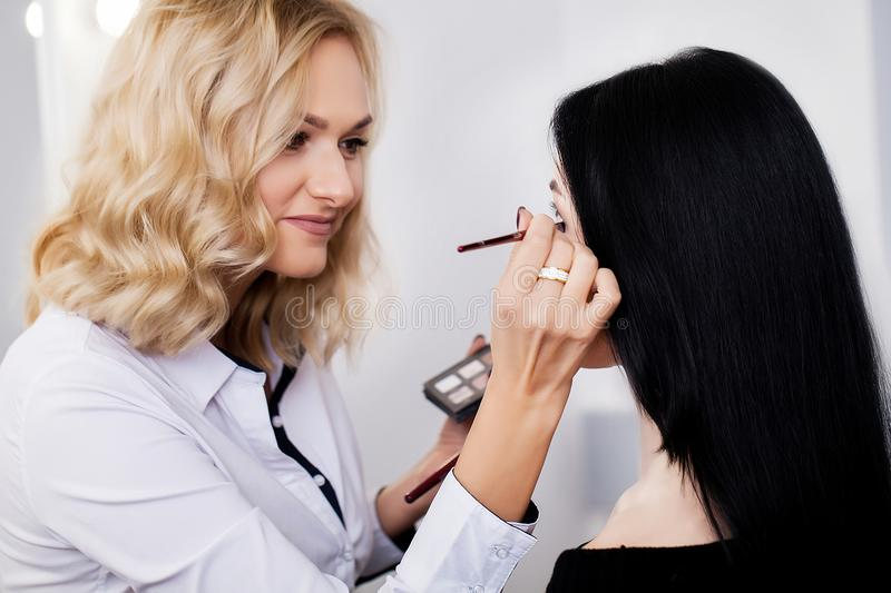 Professional makeup process. Artist is making face style.  stock image