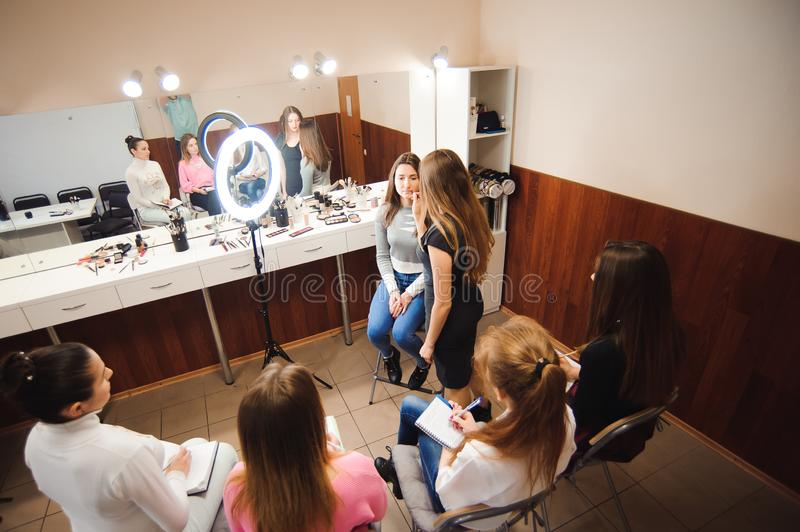 Professional makeup teacher training her student girl to become makeup artist. Makeup tutorial lesson at beauty school royalty free stock photos