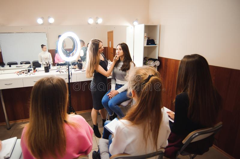 Professional makeup teacher training her student girl to become makeup artist. Makeup tutorial lesson at beauty school royalty free stock photo