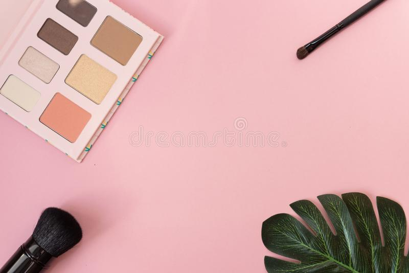 Professional makeup tools palette of multicolor cosmetic make up set with brushes and a monstera leaf on pink background. Beauty stock photography