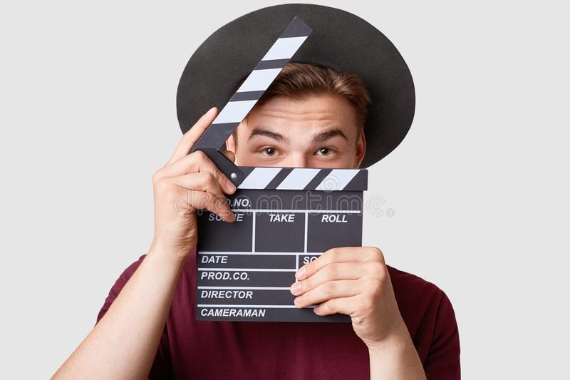 Professional male actor ready for shooting film, holds movie clapper, prepares for new scene, wears special clothes, isolated on w. Hite background. Handsome royalty free stock photo
