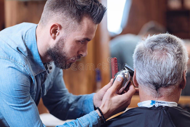 Professional male barber holding a hair cutting machine. Perfect haircut. Professional nice male barber holding a hair cutting machine and concentrating on the royalty free stock photo