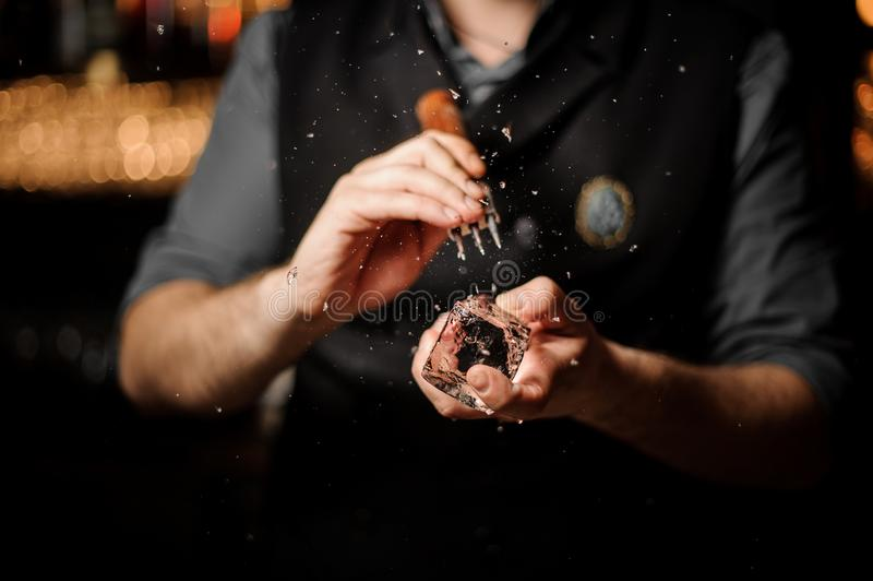 Professional male bartender making an appropriate form to the ice cube with the special tool. On the bar counter on the blurred background stock photo