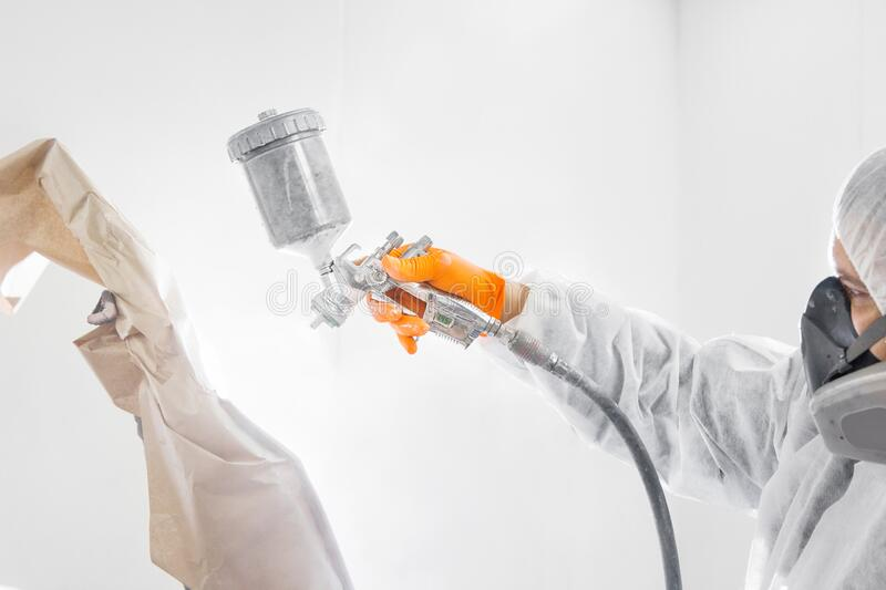 Professional male car painter is painting in garage by airbrush. Man works with spray gun. Painting the car in white. Body repair cars stock photo