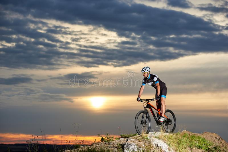 Energetic man in sportswear cycling on rock hill. Professional male cyclist cycling mountain bike on rock hill with enthusiasm. Energetic and athletic man in royalty free stock image