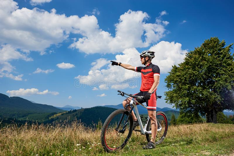 Professional male cyclist standing with bike on grassy valley, resting after cycling. Young active biker pointing to cloudy sky, enjoying view of distant stock photography