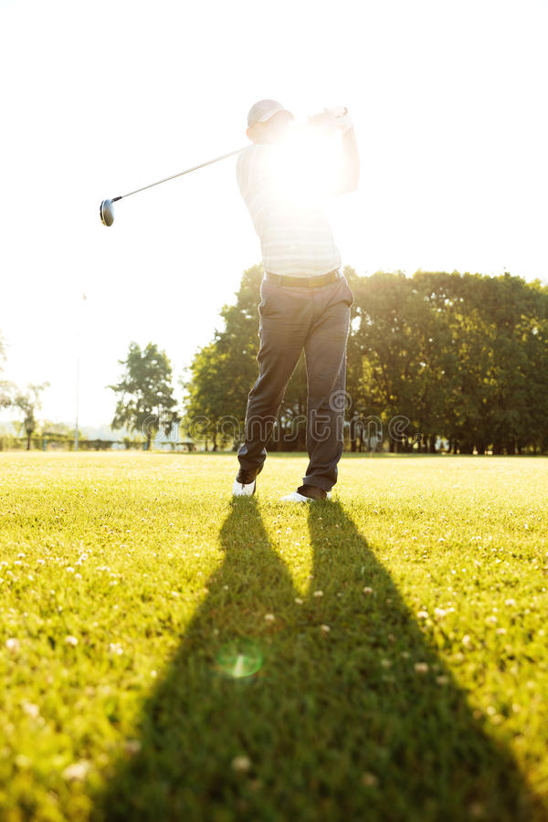 Professional male golf player hitting with a driver from a tee. Professional male golf player hitting ball with a driver from a tee royalty free stock photography