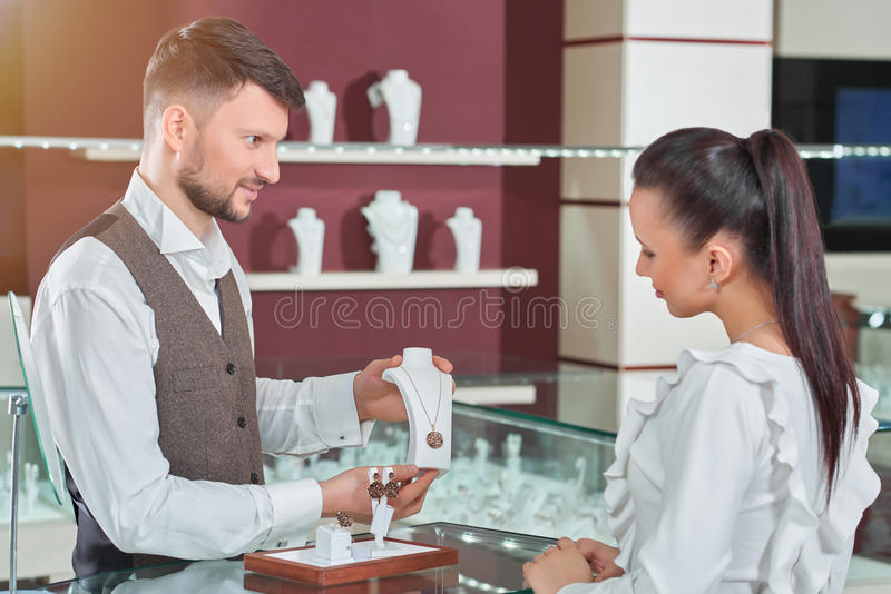Professional male jeweler helping his female customer at the sto royalty free stock image