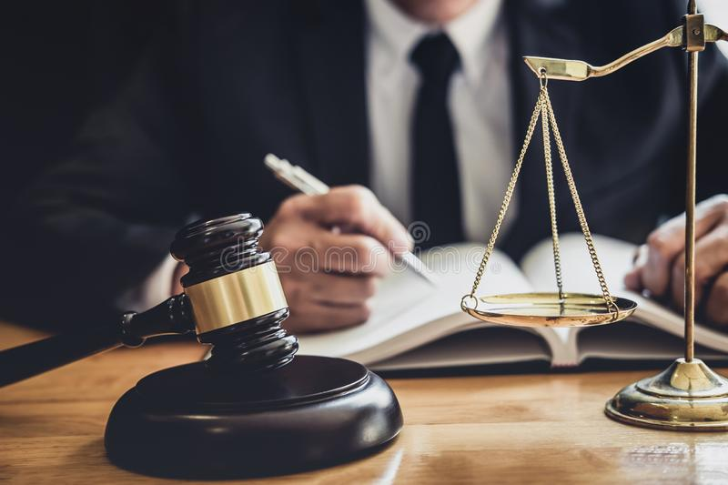 Professional Male lawyer or judge working with contract papers, documents and gavel and Scales of justice on table in courtroom, royalty free stock photo