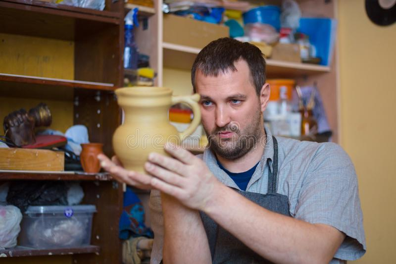 Professional male potter examining jar in pottery workshop. Professional male potter examining earthenware jar in pottery workshop, studio. Crafting, artwork and royalty free stock images