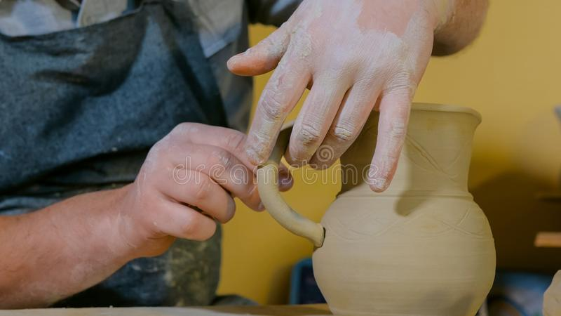 Professional male potter working in workshop, studio stock photography