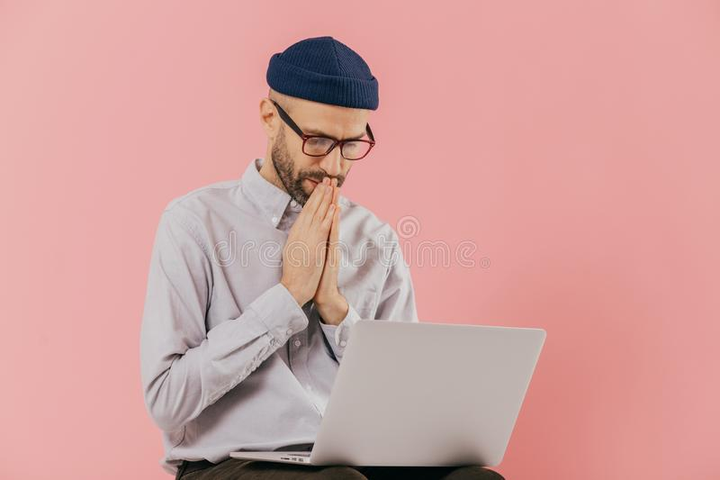 Professional male programmer keeps hans in praying gesture, looks at screen of laptop computer, believes in successful result of royalty free stock photography