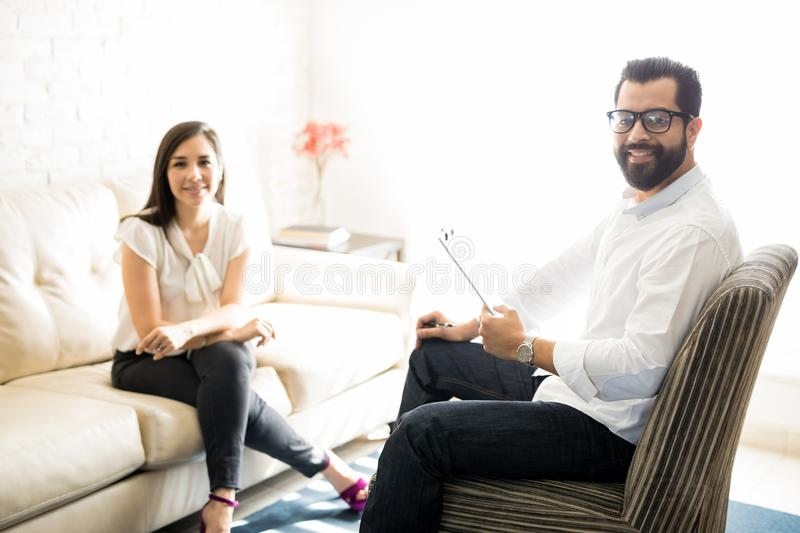 Professional male psychologist with female client. Sitting on sofa in his office royalty free stock image
