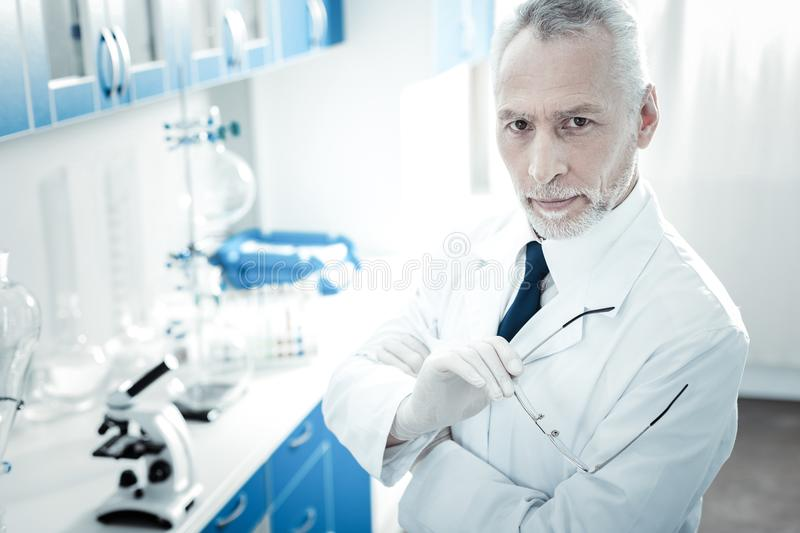 Professional male scientist holding his glasses royalty free stock photos