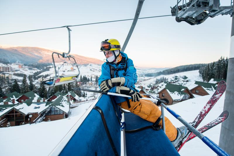 Skier guy sitting at ski chair lift in beautiful day and turns back. Close-up. Concept of skiing. Professional male skier sitting at ski chair lift in the stock photography