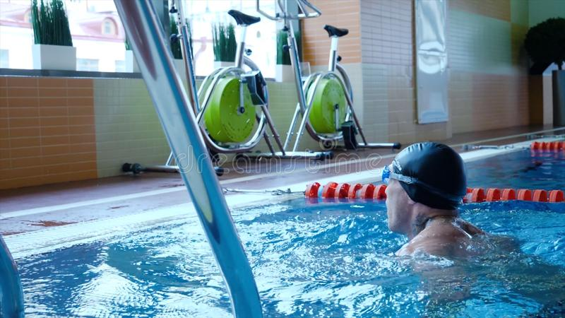 Professional male swimmer practising in swimming pool. Young sportsman swimming in pool. Slow motion.  stock photo