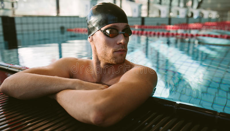 Professional male swimmer resting. Shot of young man on the edge of pool relaxing and looking away. Professional male swimmer resting royalty free stock photography
