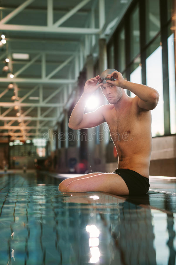 Professional male swimmer sitting on edge of a pool. Shot of professional male swimmer sitting on edge of swimming pool, putting on swimming glasses royalty free stock photos