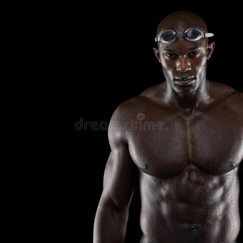 Professional male swimmer. Studio shot of professional male swimmer with copyspace. Young african man with muscular build wearing swimming glasses against black royalty free stock photo