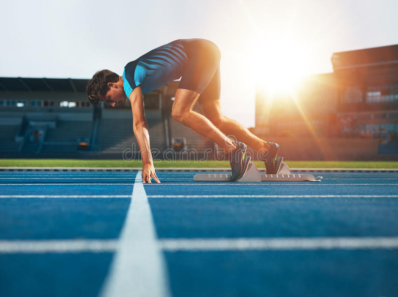 Professional male track athlete in set position. Male athlete on starting position at athletics running track. Runner practicing his sprint start in athletics stock images