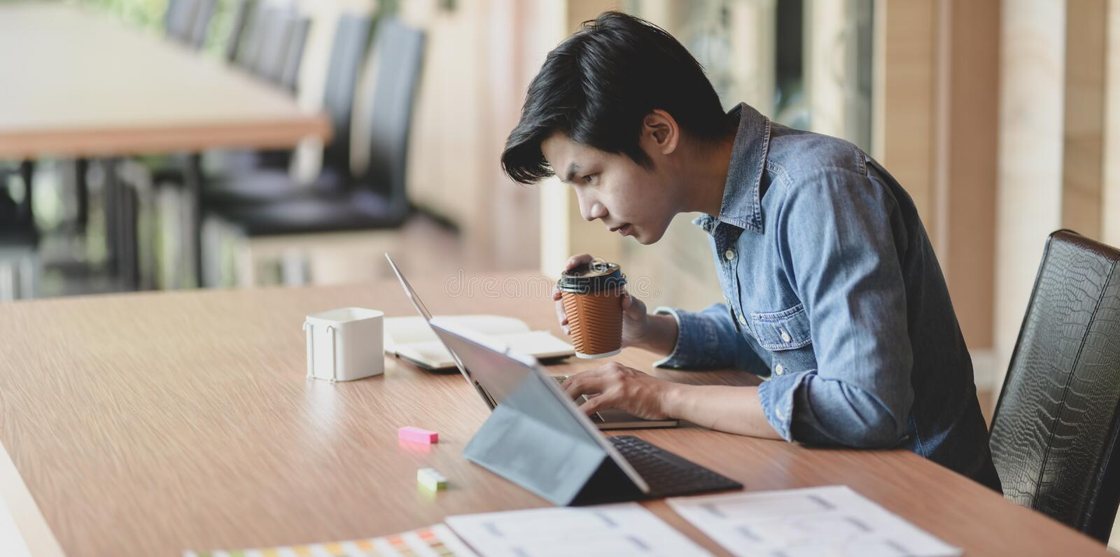 Professional male UI web developer working on his project about UX template. While using laptop computer in the office stock photo