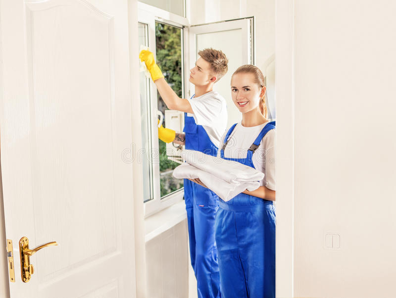Professional man cleaning window with girl in house royalty free stock photography