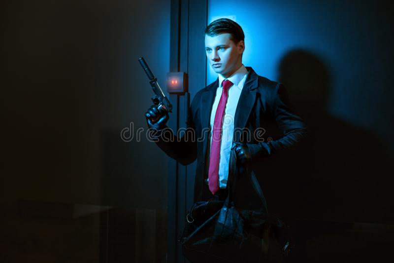 Professional man is a killer. Professional man is a murderer, in his hand a pistol with a silencer stock image