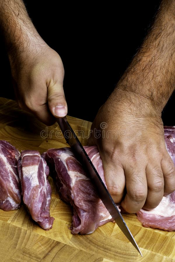Professional man`s hands cutting raw pork meat on wooden board, selective focus, close-up stock images
