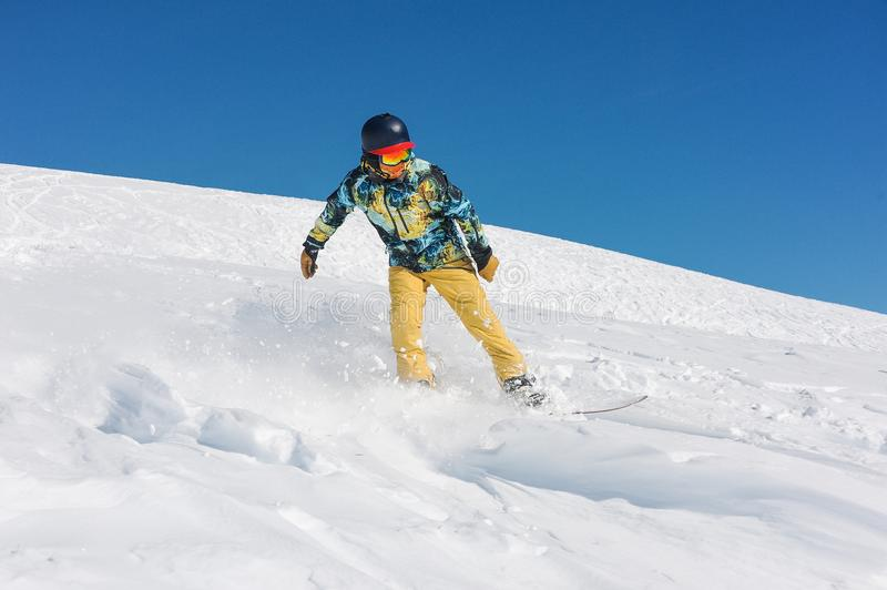 Professional man snowboarder in bright sportswear riding down a mountain slope stock images