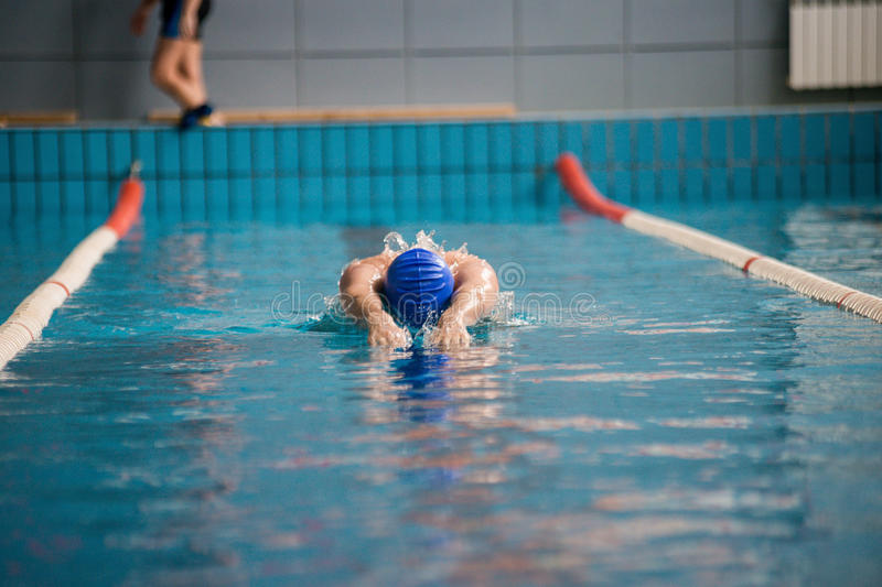 Professional man swimmer swims. The man is a professional swimmer swims in the pool quickly royalty free stock photos