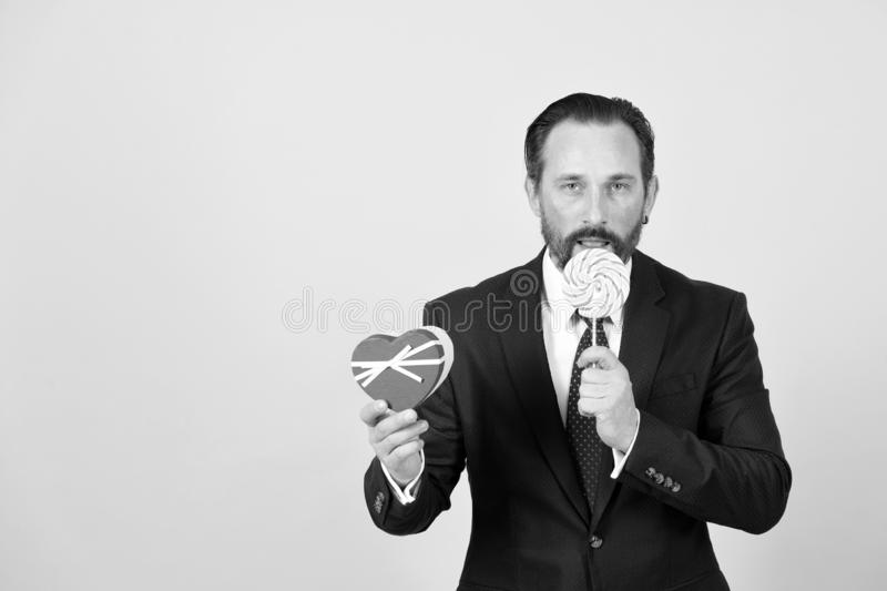 Professional manager tests big lollipop. Man hide his smile behind candy. Professional manager tests orange lollipop. Man hide his smile behind candy and makes stock image