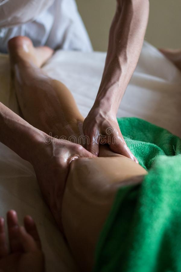Professional Masseur Doing Deep Tissue Oiled Massage to a Girl at Ayurveda Massage Session. Professional Masseur Doing Deep Tissue Oiled Leg Massage to a Girl at stock photo