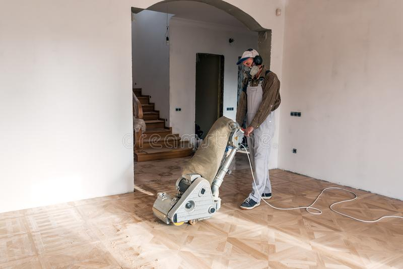 A professional master grinding a parquet stock image