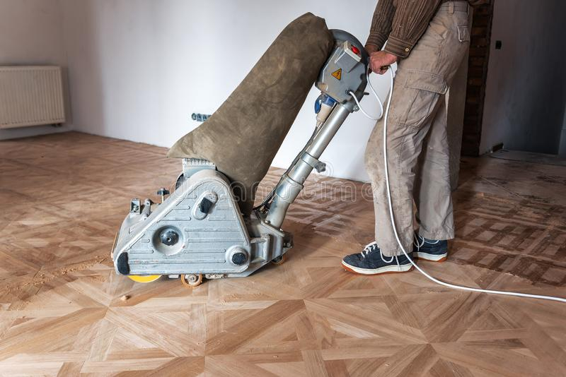 Professional master grinding a parquet royalty free stock photography